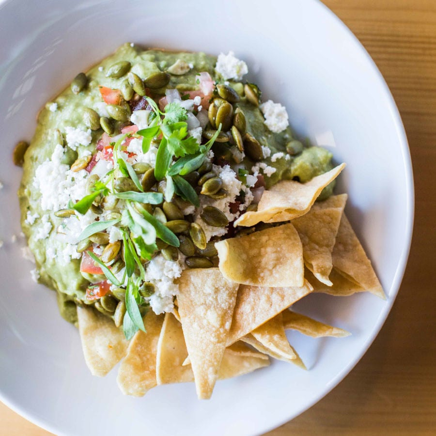 Deck out your guacamole recipe with pipits (pumpkin seeds) and queso fresco. Chefs Deigo Galicia and Rico Torres recommend serving it with tortilla chips or pork cracklins'.